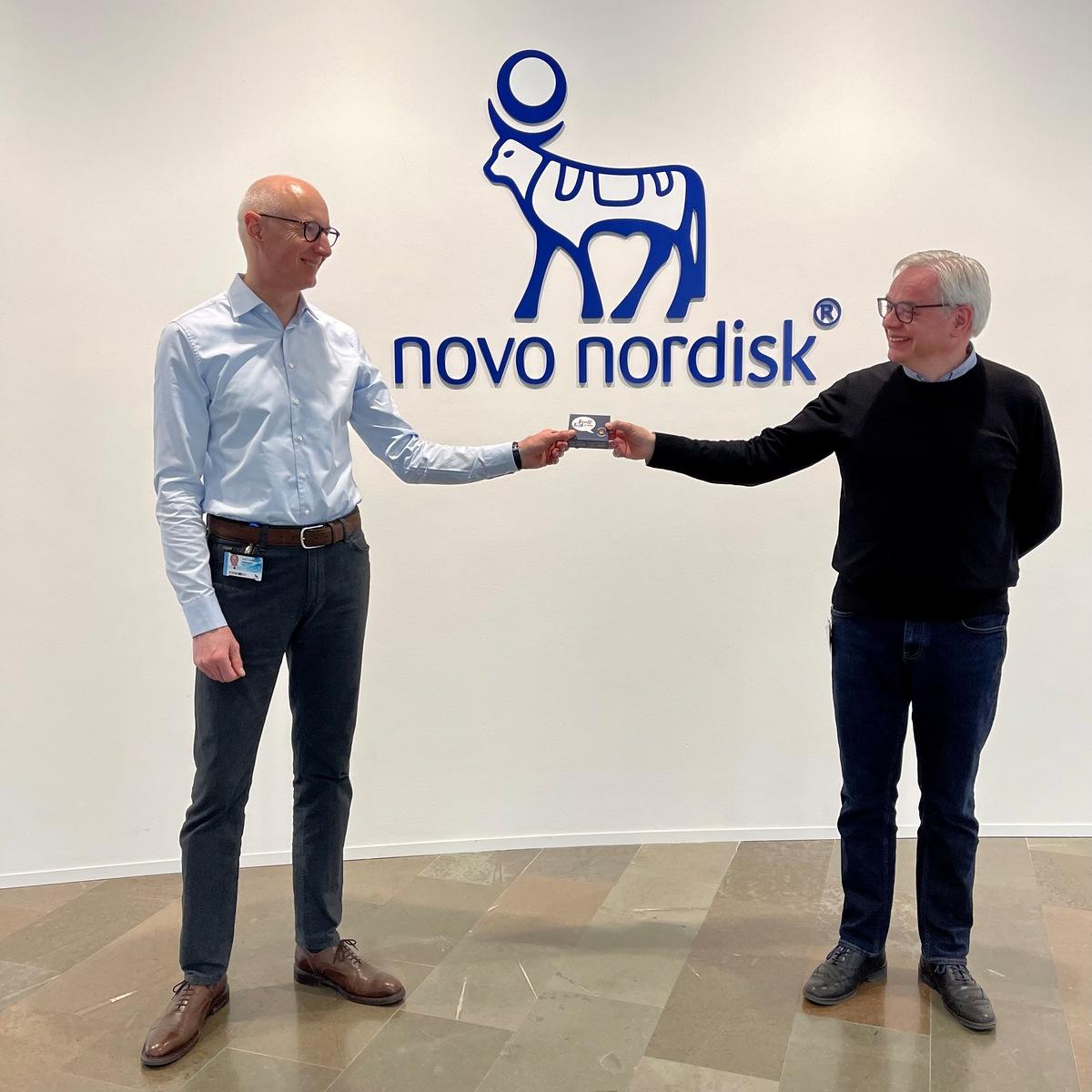 Lars Fruergaard Jørgensen, CEO i Novo Nordisk overrækker et eksemplar af spillet til Søren Ravn Jensen, direktør i Julemærkefonden