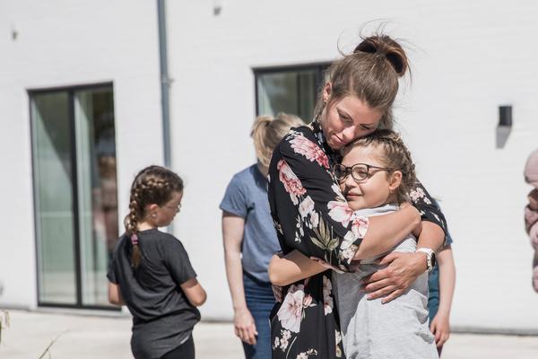 Voksen pædagog giver kram og omsorg til pige