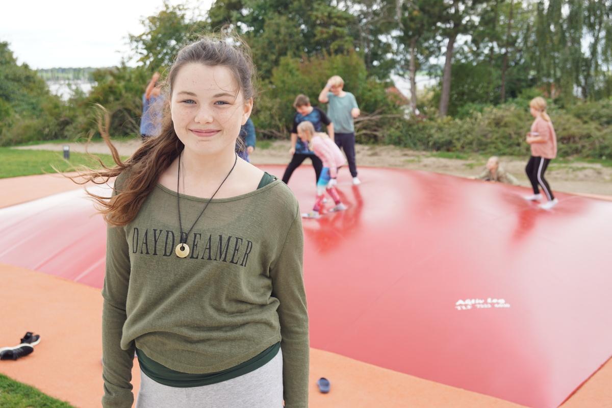 Smilende pige med fregner foran børn på trampolin